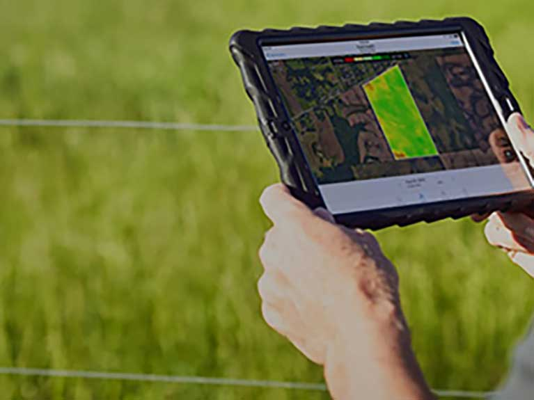 Over the shoulder view of farmer holding tablet featuring Climate FieldView in a field.