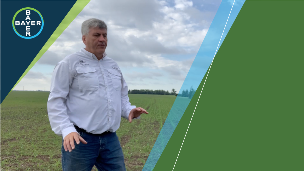 Image of Bruce Murray standing in a field talking about controlling early weeds with Roundup Xtend and Xtendimax.